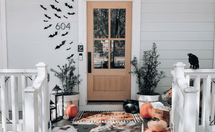 A cute Halloween front porch features bat stickers around the door and a 'Home Sweet Home' mat surrounded by mum planters, mini pumpkins and a witch's cauldron.