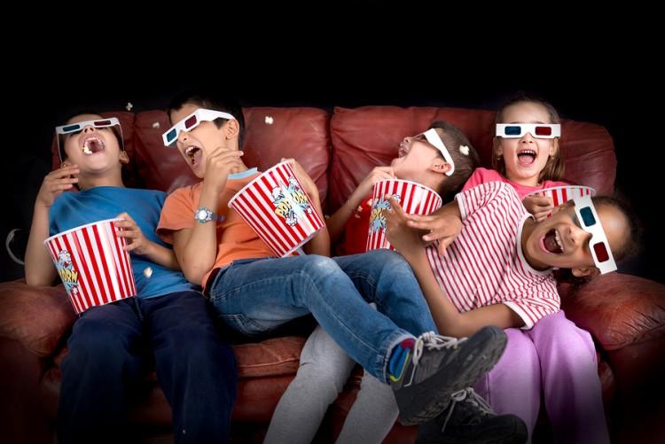 crianças fazendo uma sessão de cinema em casa nas férias