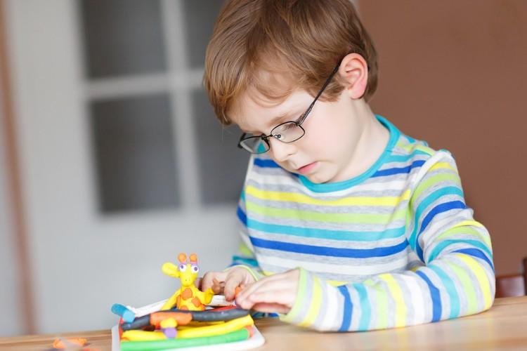 menino brincando com massinha nas férias de verão