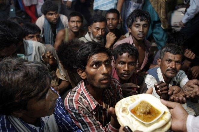 11. Hombres sin hogar esperan para recibir comida gratuita, en Nueva Delhi, India.
