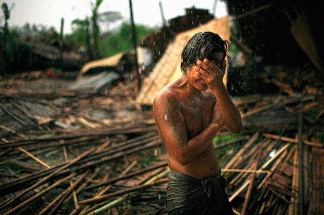 18. Hhaing The Yu, de 29 años, se tapa el rostro con su mano mientras la lluvia cae sobre los restos diezmados de su casa. En mayo de 2008, el ciclón Nargis dejó a millones sin hogar y se cobró más de 100.000 vidas.