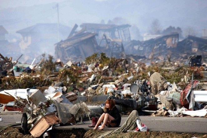 22. Una mujer se sienta en medio de los escombros causados ??por un terremoto y el posterior tsunami, en Natori, el norte de Japón, Marzo 2011.