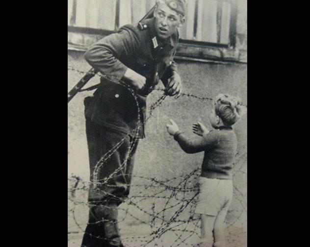 4. Berlín dividido: Tras la guerra, Alemania queda dividido en este y oeste. En la foto, se retrata algo que sucedió en muchísimos casos: Una familia quedó dividida. El soldado ayuda a un chico a cruzar para encontrala.