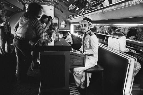 11. Elton John tocando el piano en su avión privado, 1976.