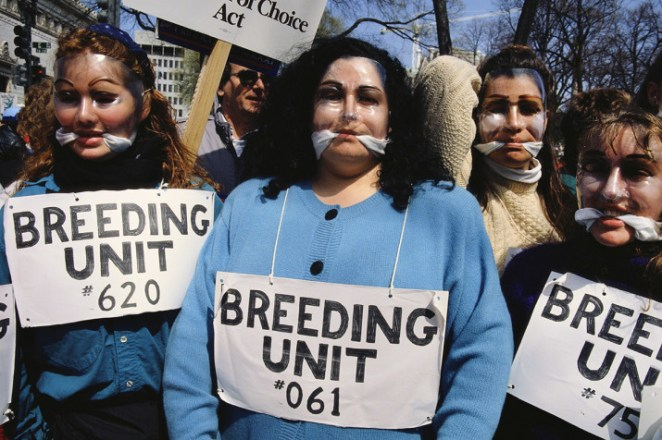 Women wear signs and masks during an abortion rights march in Washington, DC, in 1992.