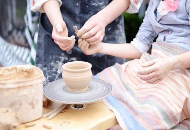 Hands working on throwing wheel, master class of studio pottery