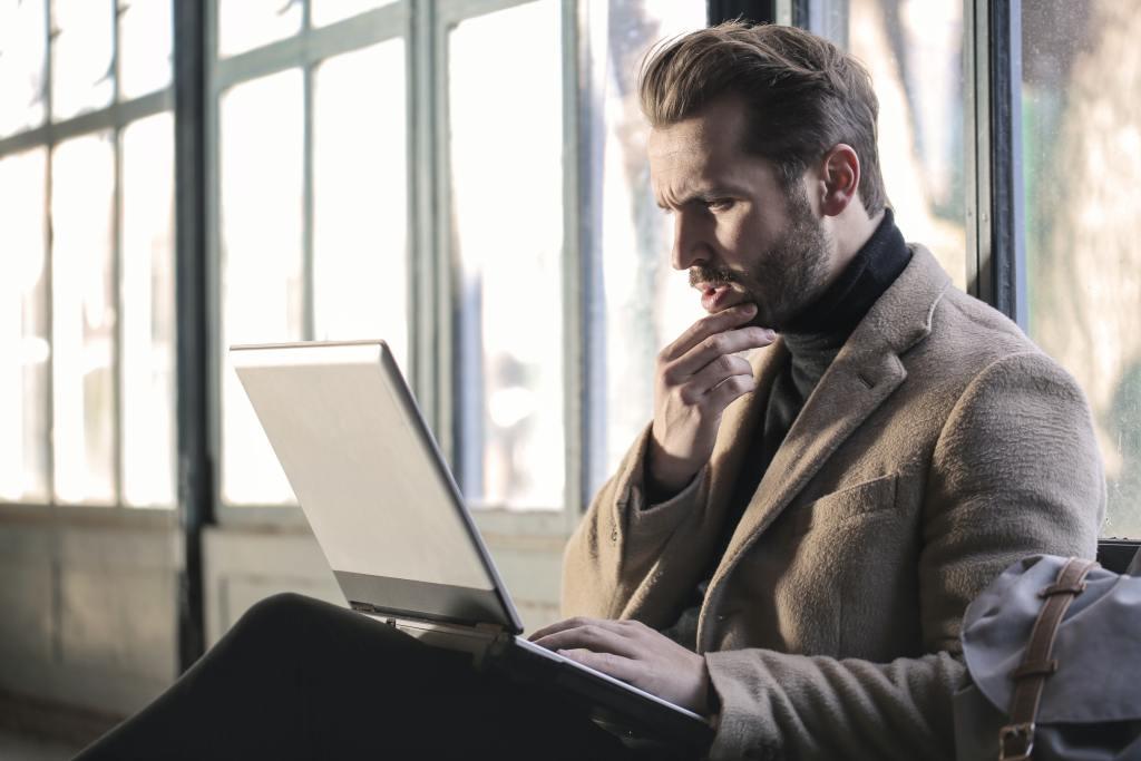 Homem com a mão no queixo olhando para o computador, pensativo.