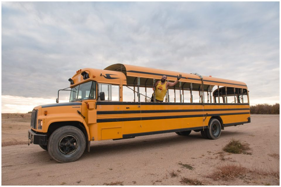 Man hangs out of school bus conversion no windows roof raised western canada wedding photographers