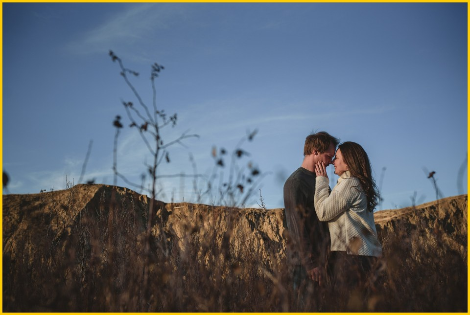 adventure engagement sessions in saskatchewan landing couple standing in front of butte outcropping on horizon
