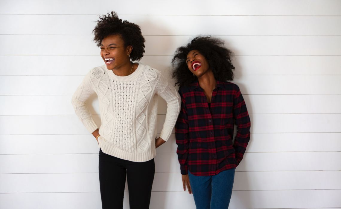 Best Friends Laughing in Front of Wall