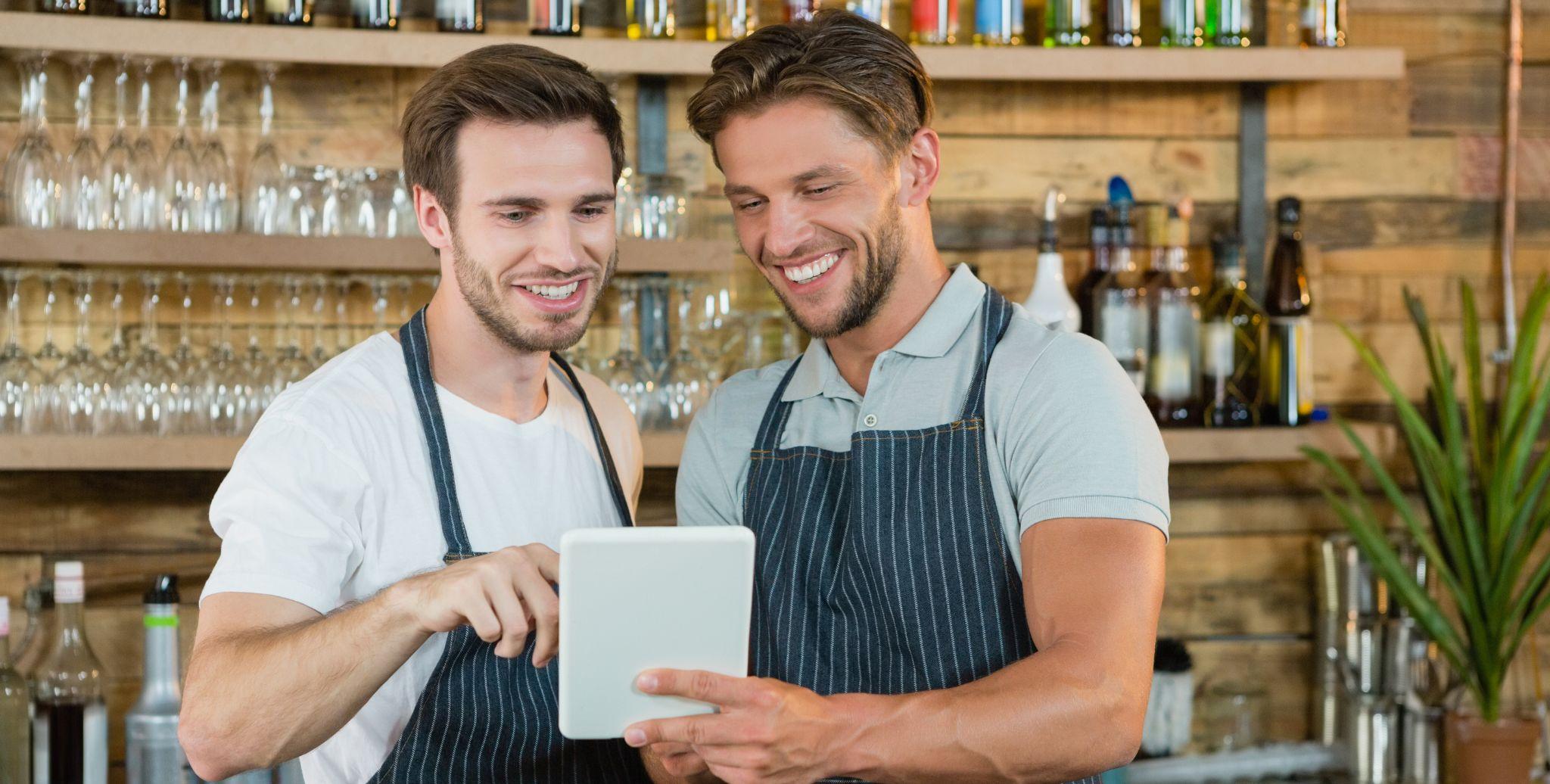 Hommes serveurs sourient devant iPad