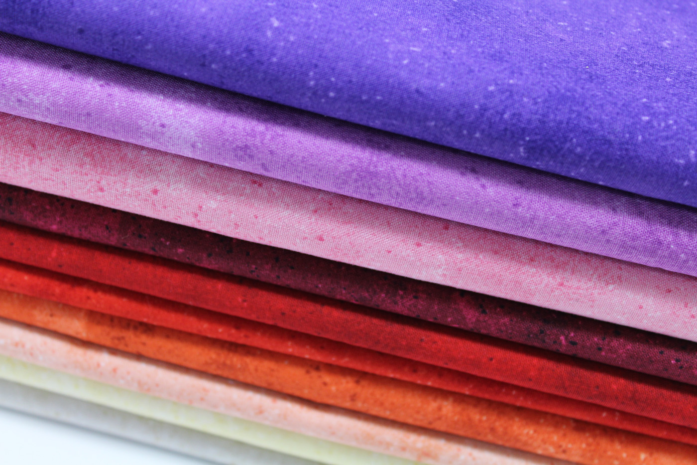 Quilting cotton design Shadowplay photo colours cream, oranges, red, pinks and purples