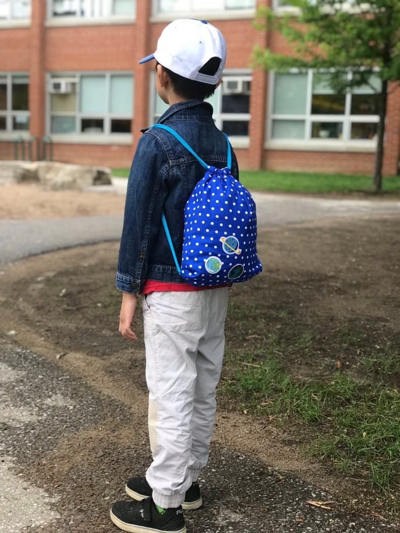 Photo of a young boy using the drawstring backpack at school.