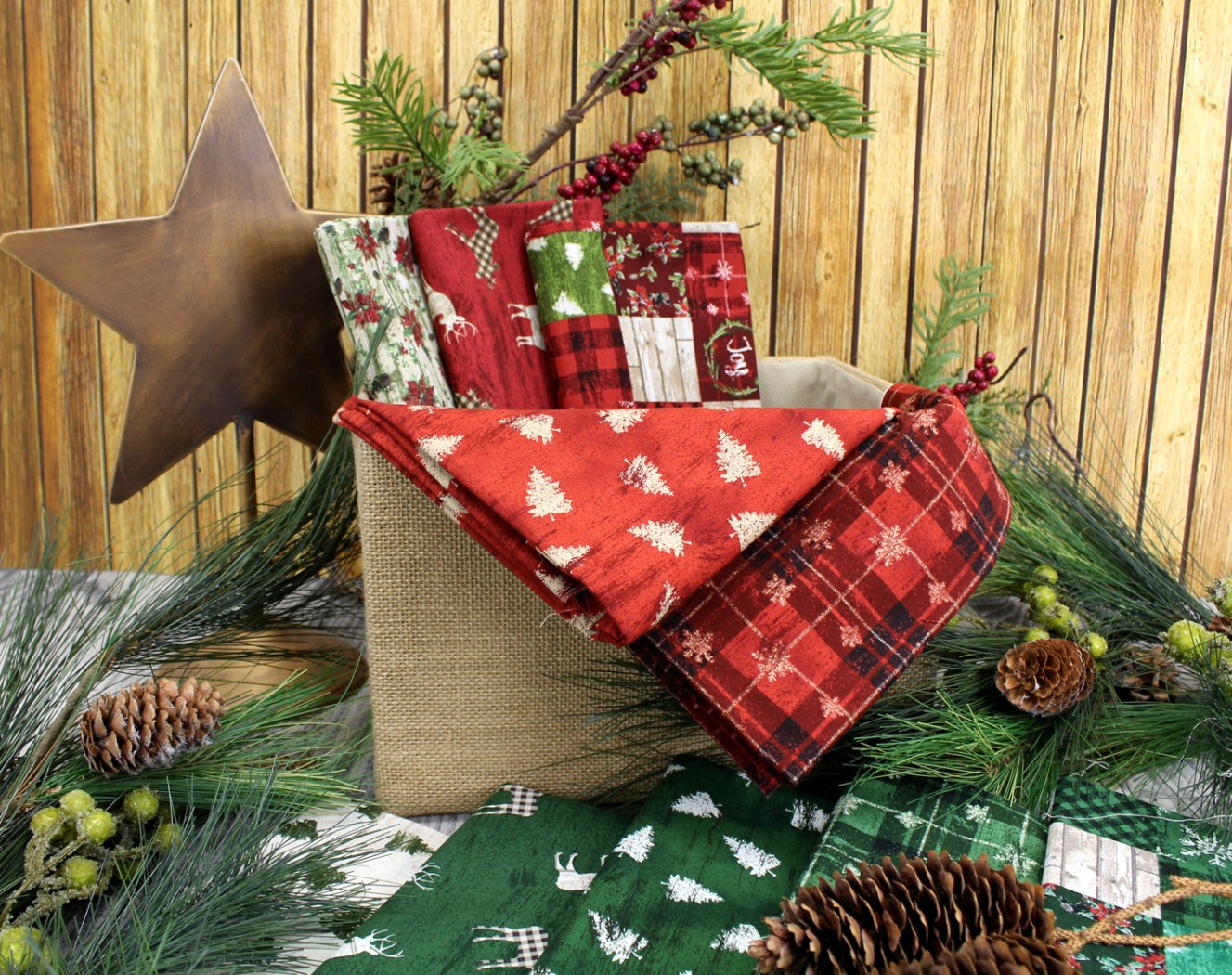 photo of the Country Christmas cotton fabric group in traditional reds and green with wood and pinecones