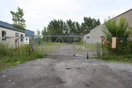 A fenced-off empty lot sits unused