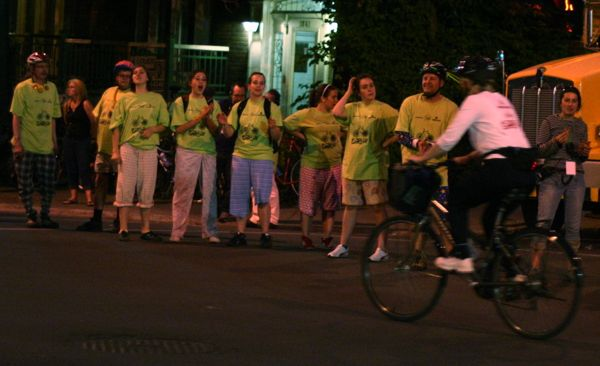 Volunteer cheerleaders - in what look like pyjamas - get the cyclists going.