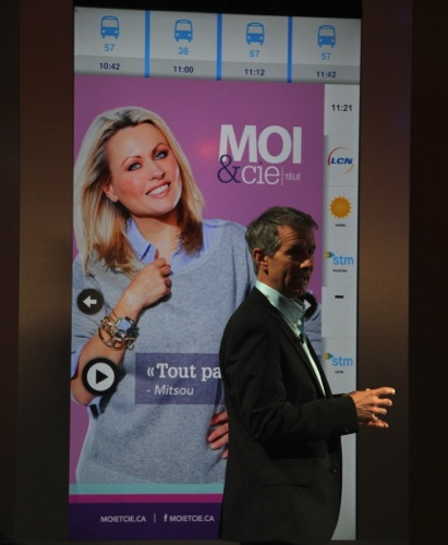 Quebecor out-of-home VP Claude Foisy demonstrates the new interactive screen