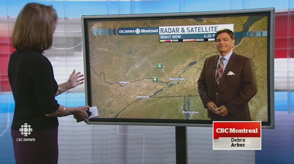 Debra Arbec looks at live video of weather specialist Frank Cavallaro