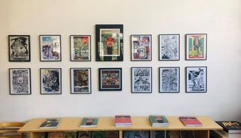 A photo of the S. Clay WIlson display at the Fantagraphics bookstore, showing art prints above Wilson's books.
