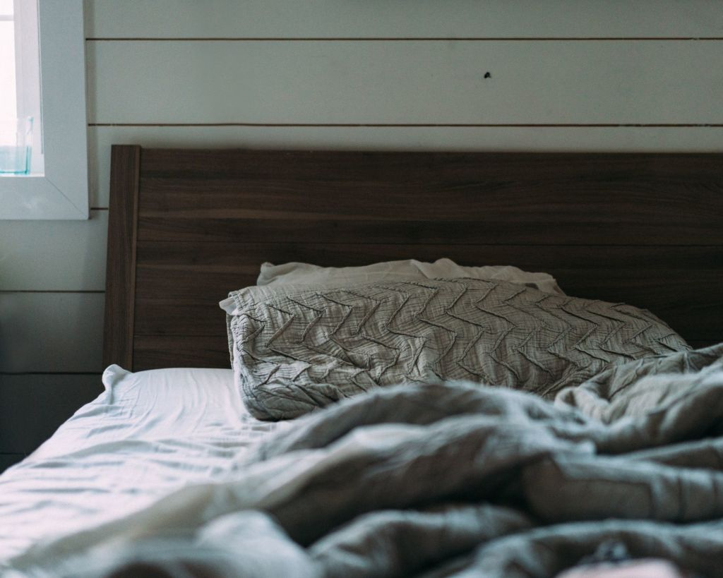brown wooden bed with gray bedspread set