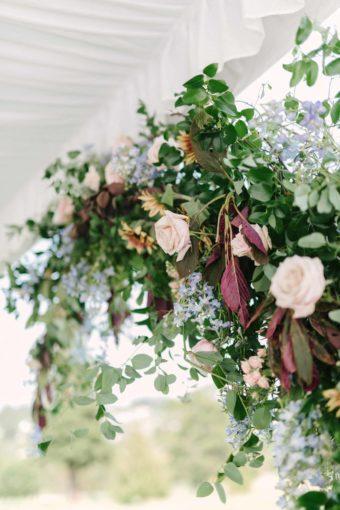 ceremony arbor with ponk roses, blue delphinium, smoke bush