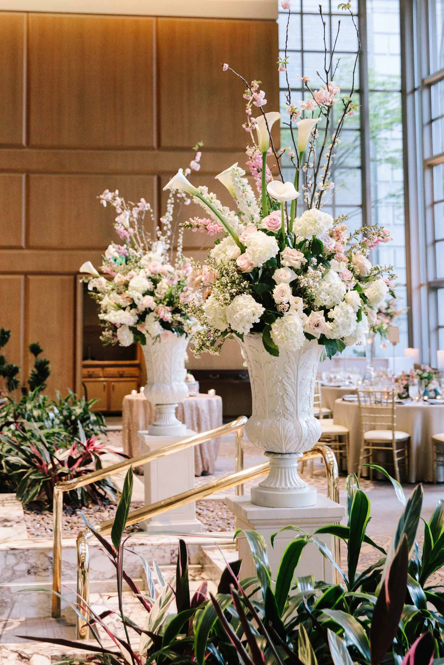 white urns filled with spring garden wedding flowers