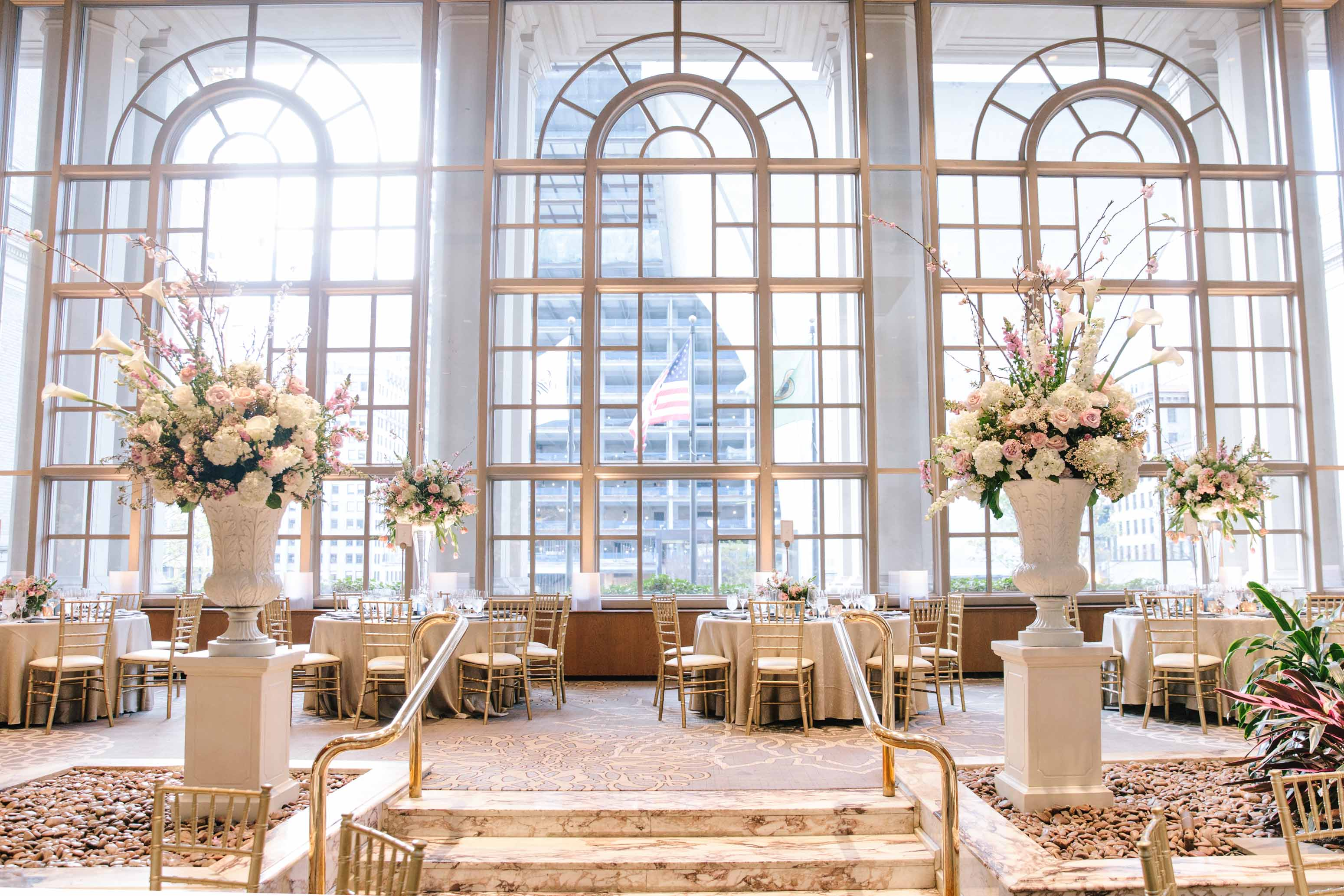 Tall spring centerpieces on tables in ballroom, in front of large conservatory windows