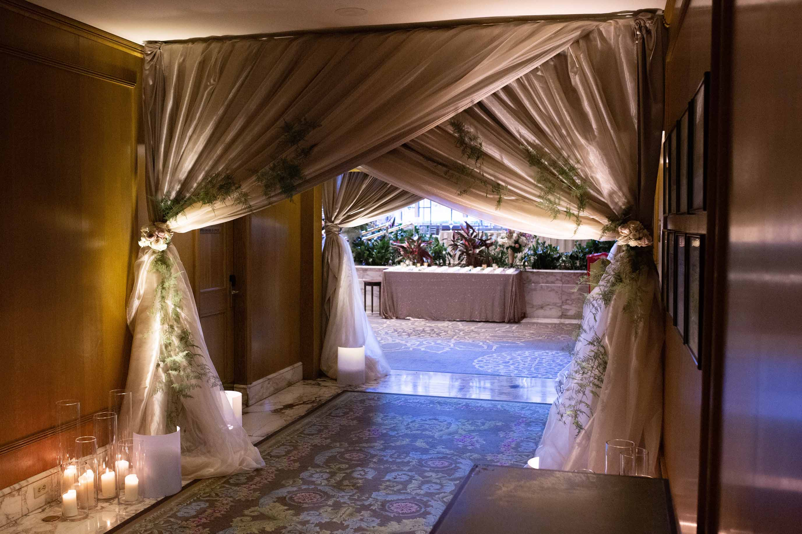 Shadowed draped entryway leading into wedding reception