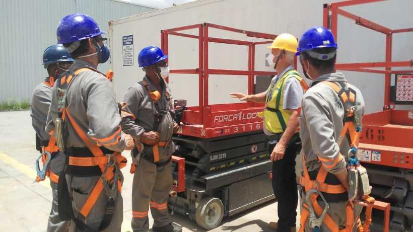 treniamento de trabalho em altura, técnico realizando o treinamento e explicando ao funcionários o funcionamento da plataforma tesoura