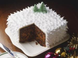 Fruit cake coated with spiky white icing and decorated with christmas trees, one slice removed