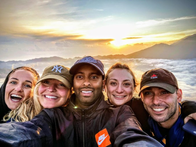 A group of people taking a selfie in front of a sunrise above the clouds.