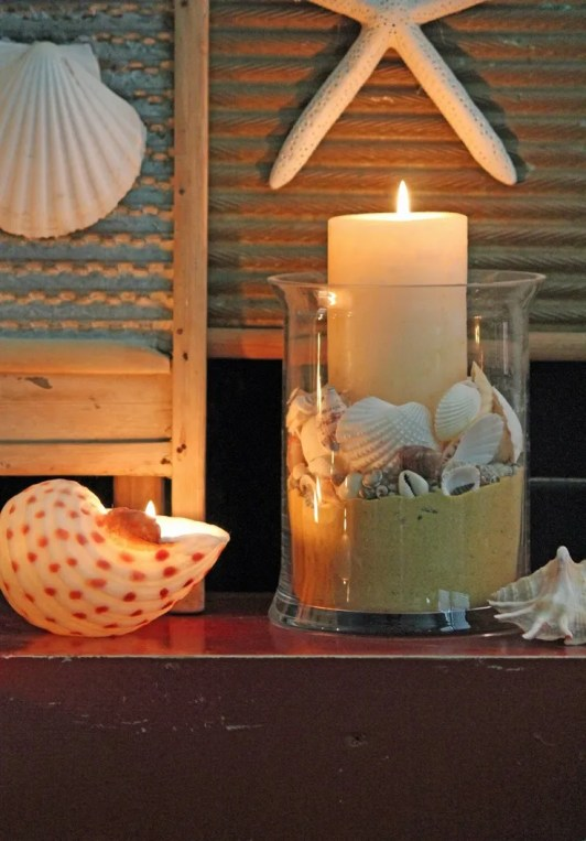 Glass vase with sand, shells and candle