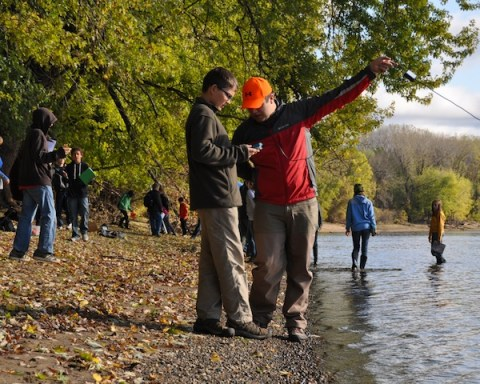 Science teacher Shane guides a 7th grader as he measures the Mississippi River.