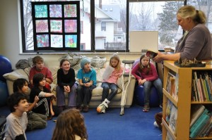 Kak reads aloud from the book The Watsons Go to Birmingham to her third and fourth grade class.