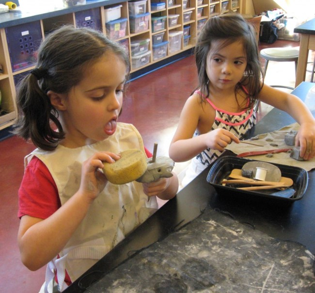Kindergarteners experiment with clay tools.