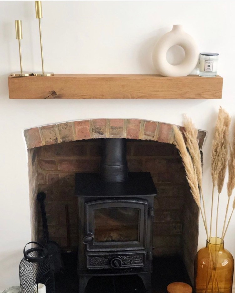 solid oak beam on a white fireplace wall above exposed brickwork hearth