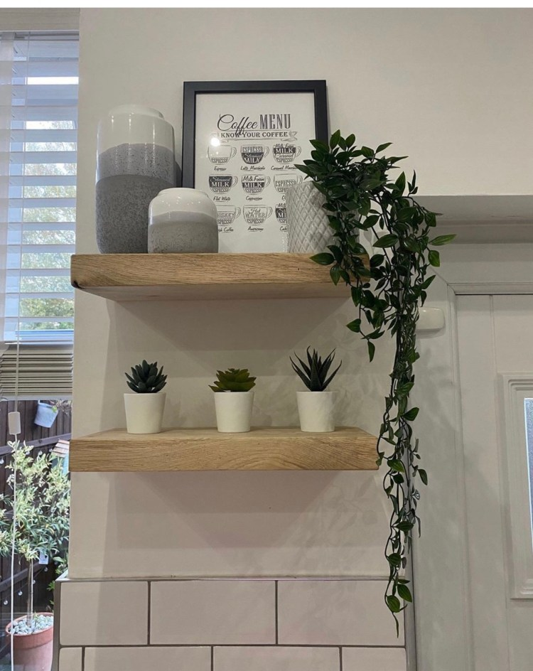 oak floating shelves in a kitchen above white brick tiles.