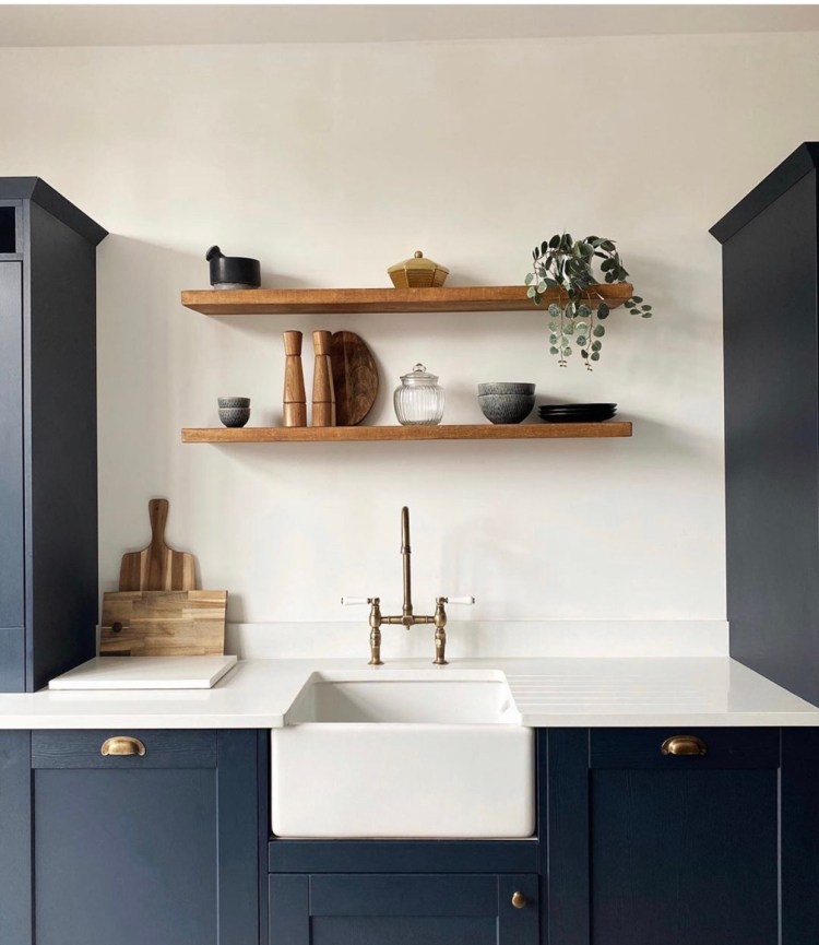 dark blue kitchen with belfast sink and floating shelves on white wall.