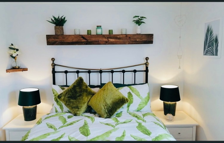 white bedroom with tropical theme and floating shelf above bed