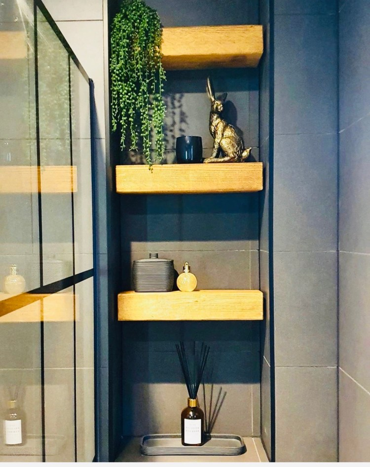 three floating shelves in a bathroom alcove