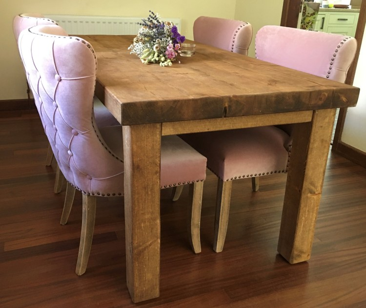 solid wood handmade dining table with pastel pink chairs
