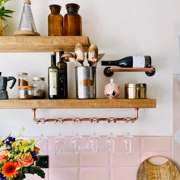 rustic floating shelves with copper wine glass holder in pink kitchen