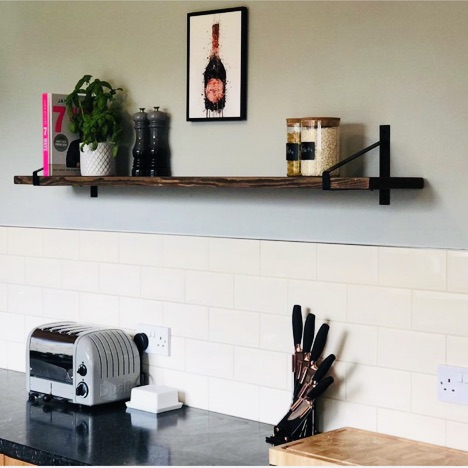dark kitchen shelf above brick tiles on grey/green wall.