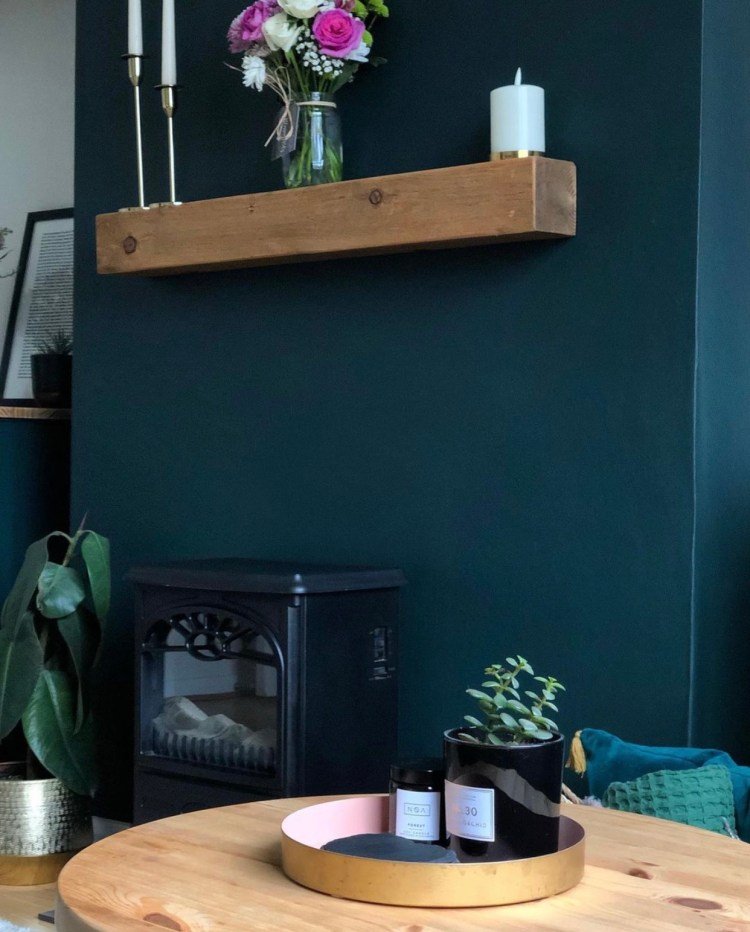 solid oak mantels on a dark green fireplace wall above a wood burner.