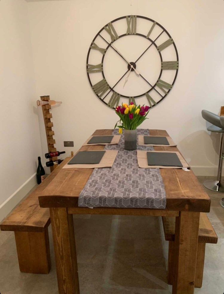 solid rustic chunky wooden dining table with benches with giant clock on the wall.