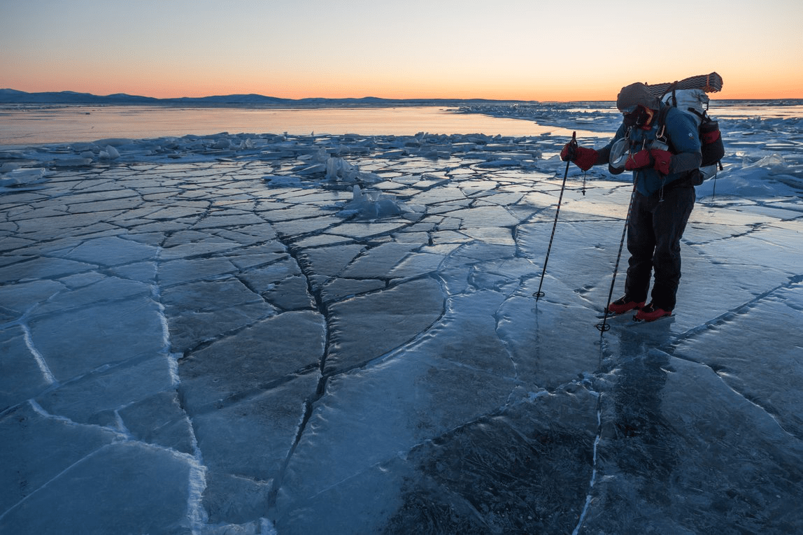 Greg Mills in his ice skates wearing a backpack, standing on cracked ice in Alaska. A beautiful pastel sunset behind him.