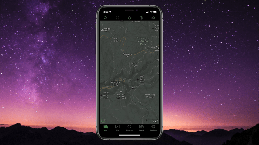 A cell phone with the screen displayng a topographical map in Dark Mode, with a dark colored map and light colored writing.  The phone is set against a colorful sunset backdrop.