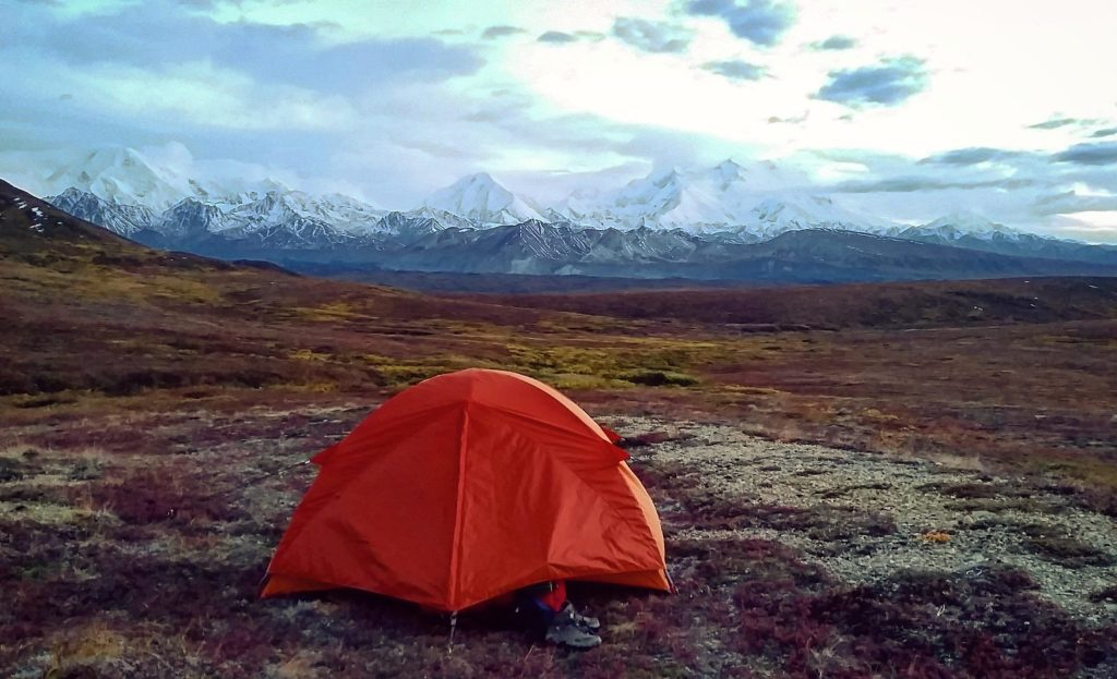 An orange tent in a mountain valley with snowy peaks in the distance.