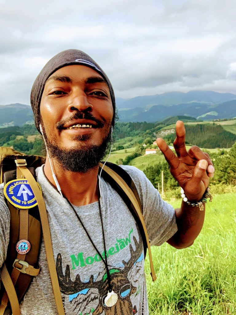 Close -up of Daniel White known by his trail name the Blackalachian  giving the peace sign with green rolling hills in the background.