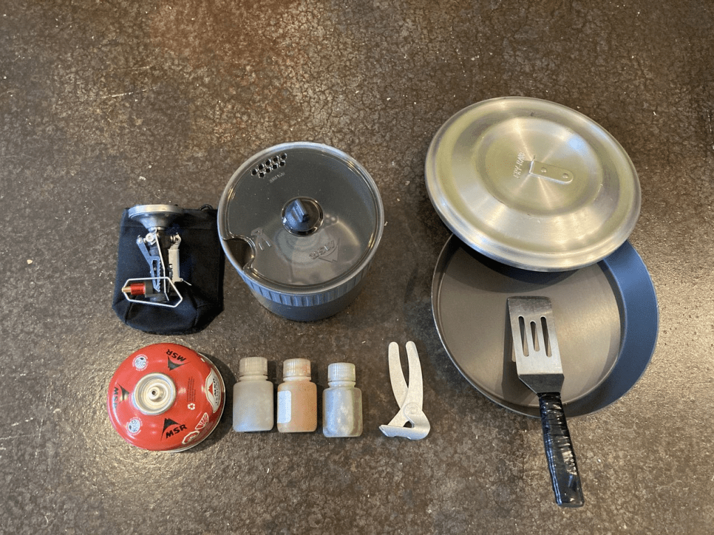 Backpacking kitchen including stove, fuel, pot, pan, spatula, spices and handle for pot.